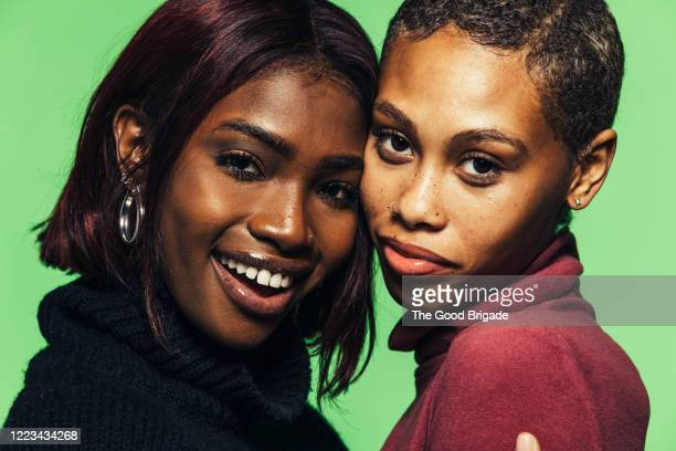 Portrait of two young women on green backdrop
