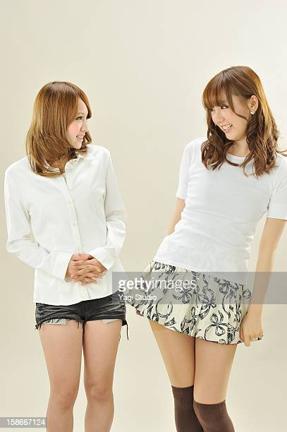 portrait of two young women - japanese short skirts stock photos and pictures