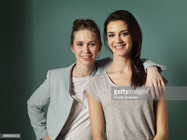 portrait of two young women - arm around stock pictures, royalty-free photos & images
