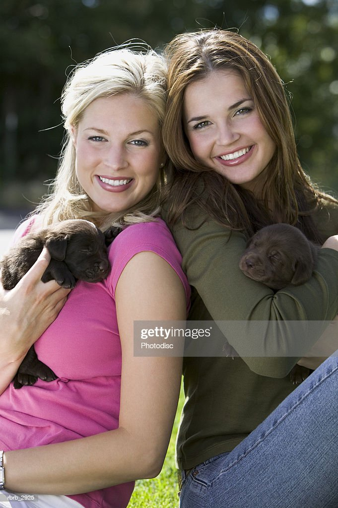 Portrait of two young women sitting holding two puppies : Foto de stock