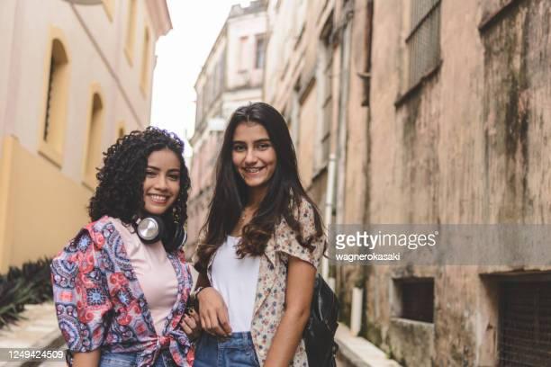 verticale de deux jeunes femmes souriant - cheveux naturels photos et images de collection