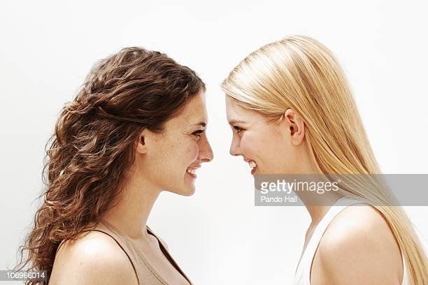 Portrait of two young women smiling, side view