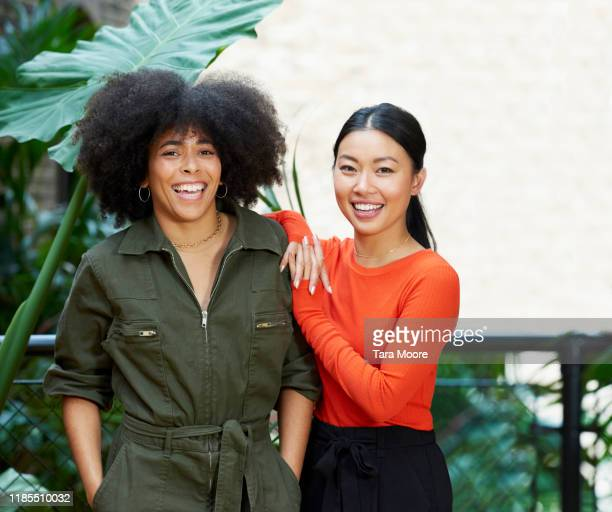 portrait of two young women smiling to camera - two people stock pictures, royalty-free photos & images