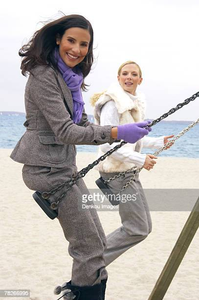 Portrait of two young women swinging on the beach