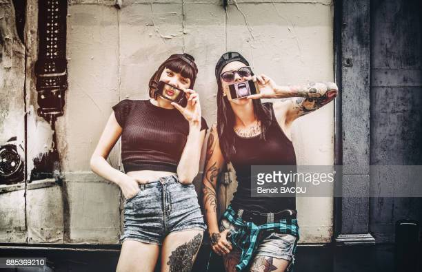 portrait of two young women, the phone in front of the mouth in front of a wooden wall - protruding stock pictures, royalty-free photos & images