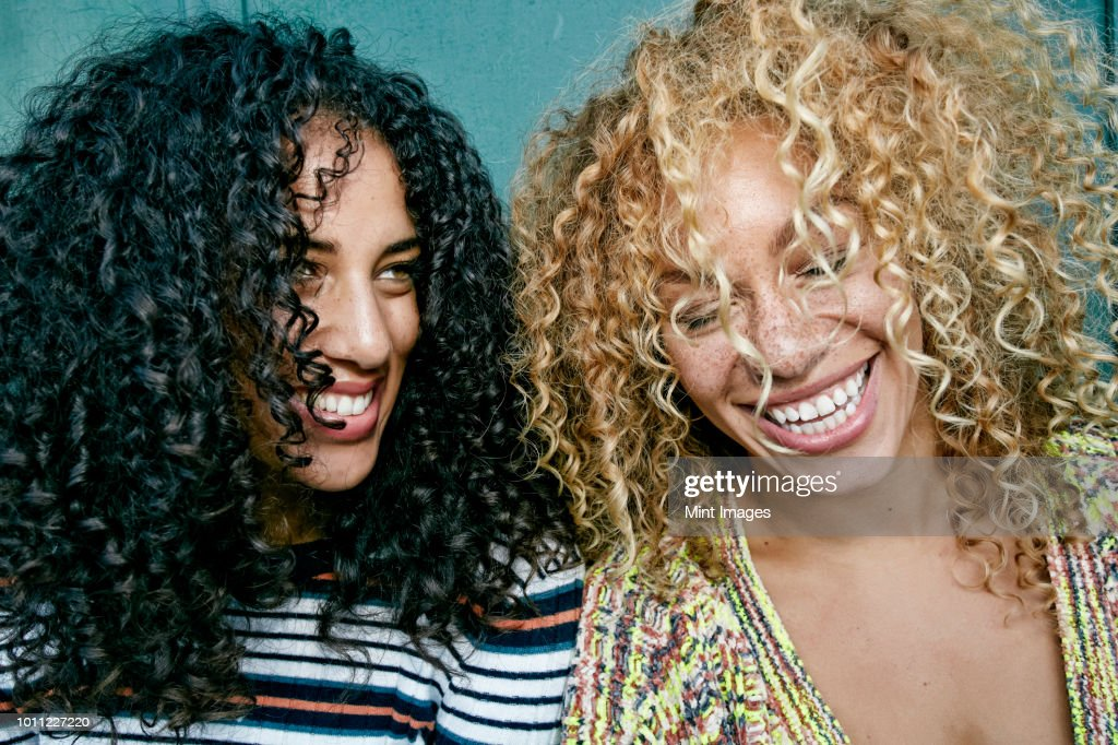 Portrait of two young women with long curly black and blond hair, smiling and laughing. : Stock Photo