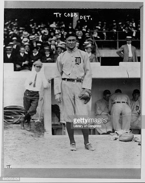 Portrait of Ty Cobb in front of a dugout during a game.