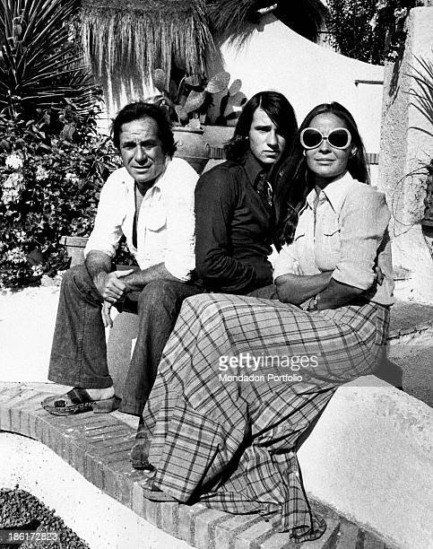 Portrait of Ugo Tognazzi Ricky son of Ugo and Pat O'Hara and the actress Franca Bettoja wife of the Italian actor they sit together on a litte wall...