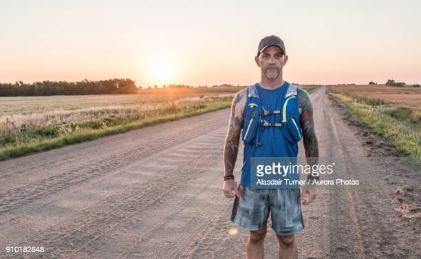 portrait of ultra runner training on rural roads of kansas outside wichita, usa - wichita stock pictures, royalty-free photos & images