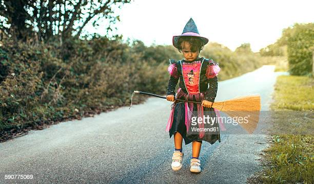 Portrait of unhappy little girl masquerade as a witch