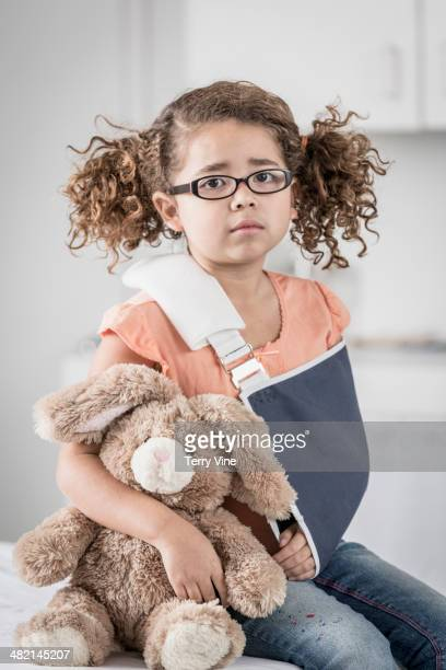 Portrait of unhappy mixed race girl with arm in sling