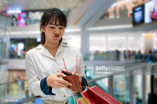 portrait of unhappy stressed beautiful person looking in open wallet with shocked expression while holding color shopping bags at mall. young model spent too much money during shopping time - commerciële activiteit stockfoto's en -beelden
