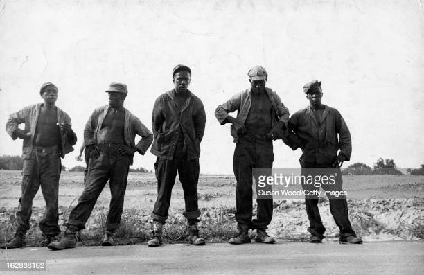 Portrait of unidentified prisoners in a chain gang as they stand next to a rural road in the Mississippi Delta Mississippi 1952