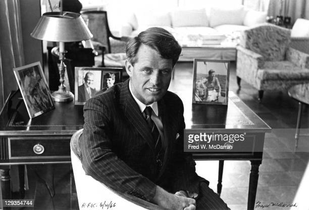 Portrait of United States Senator Robert F Kennedy as he sits at a table covered in framed family photographs in his home New York New York June 20...