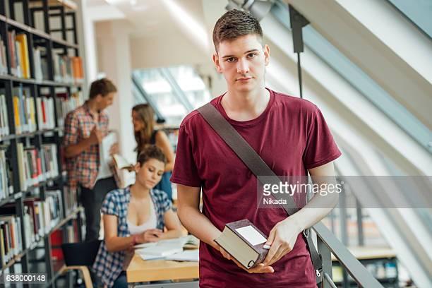 Portrait of university student holding book