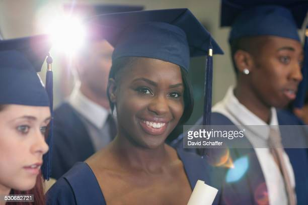 Portrait of university student holding diploma during graduation ceremony