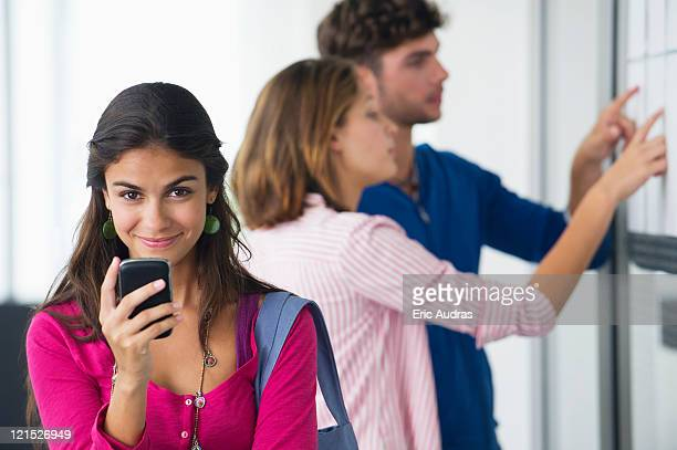 Portrait of university students using a mobile phone while friends checking for test results in bulletin board