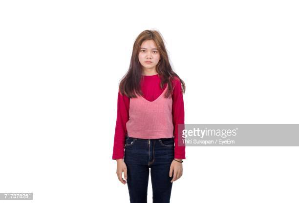 Portrait Of Upset Teenage Girl Standing Against White Background