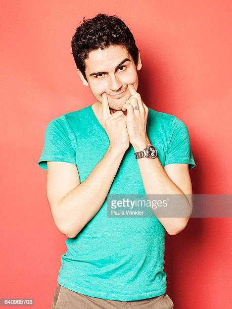 Portrait of upset young man making artificial smile against red background