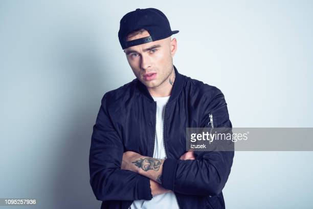 portrait of upset young man wearing bomber jacket - rap stock pictures, royalty-free photos & images