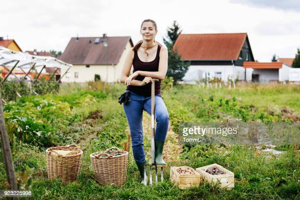 portrait of urban farmer standing with days harvest - farmhouse stock pictures, royalty-free photos & images