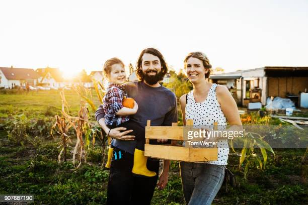 Portrait Of Urban Farming Family Together At Their Plot
