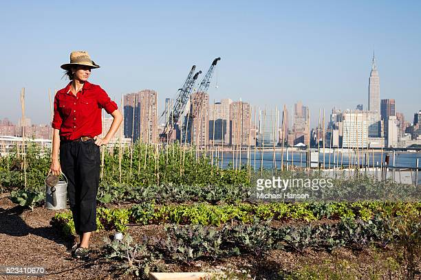 Portrait of urban female farmer holding watering can, Brooklyn, New York City, New York State, USA