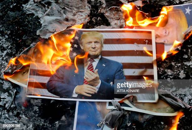 TOPSHOT A portrait of US President Donald Trump burns during a demonstration in the capital Tehran on December 11 2017 to denounce his declaration of...