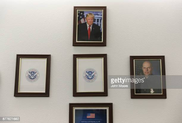 A portrait of US President Donald Trump hangs over empty frames at the US Border Patrol office on November 22 2017 in Van Horn Texas Key positions in...
