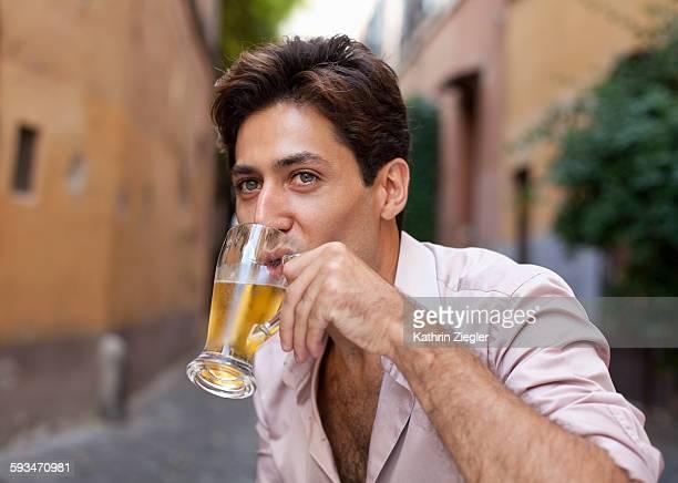 portrait of very handsome man drinking beer