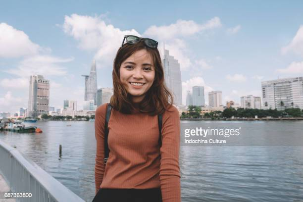 Portrait of Vietnamese beautiful girl with toothy smile, morden building on background