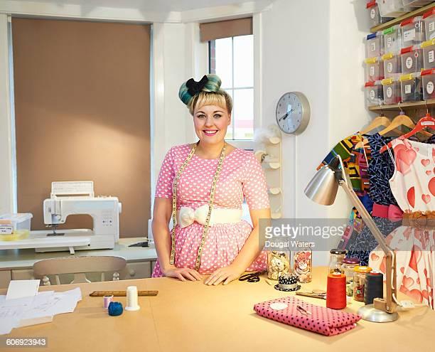 Portrait of vintage dress maker in work space.