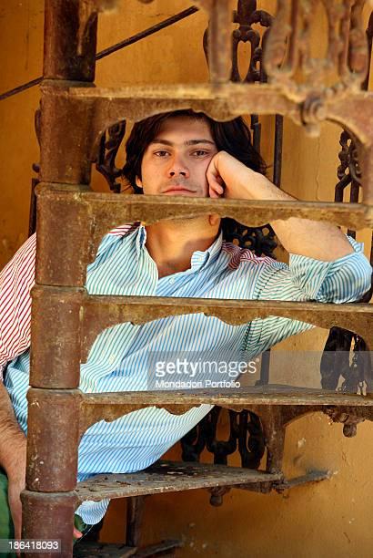 Portrait of Vittorio Sgarbi's son Carlo Sgarbi Brenner sitting on a winding staircase of Villa Banfi. Vimercate, 2000s.