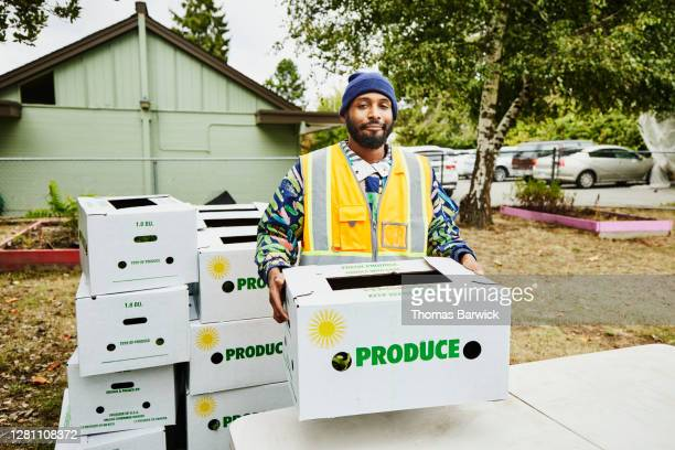portrait of volunteer at community center giving away csa boxes - hero and not superhero stock pictures, royalty-free photos & images