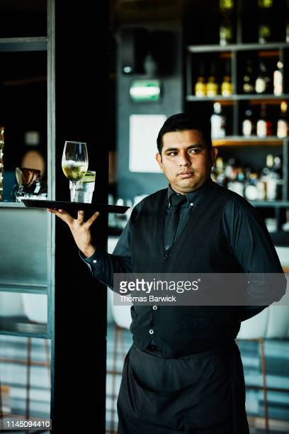 portrait of waiter carrying try of drinks in restaurant - 紺色 ストックフォトと画像