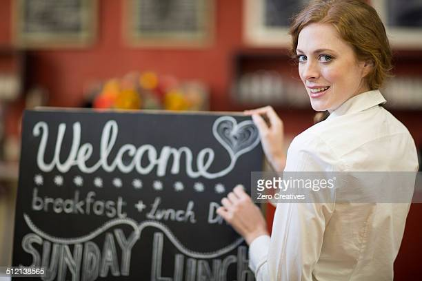 Portrait of waitress chalking menu on blackboard in restaurant