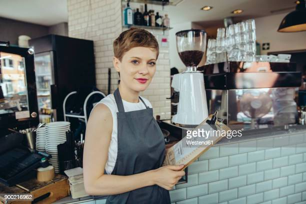 portrait of waitress holding menu in a cafe - waitress stock pictures, royalty-free photos & images
