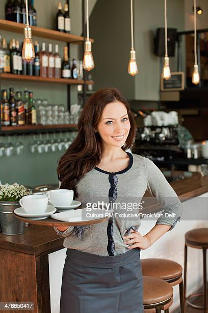 Portrait of waitress holding tray in restaurant