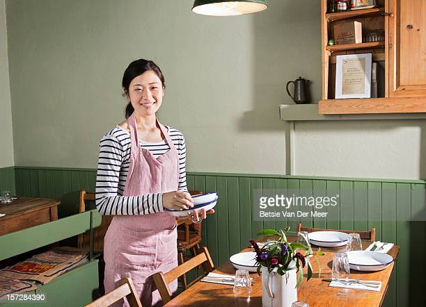 Portrait of waitress preparing table in restaurant