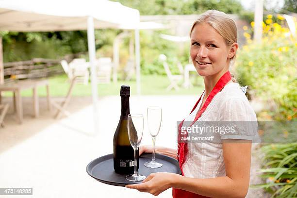 Portrait of waitress with tray of wine and glasses in cafe garden