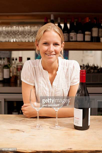 Portrait of waitress with wine bottle and glasses at kitchen counter
