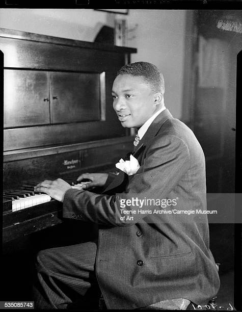 Portrait of Walt Harper wearing dark pinstriped suit with light colored handkerchief playing upright piano in interior Pittsburgh Pennsylvania 1943