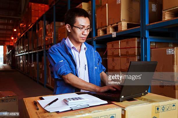 Portrait of Warehouse Businessman with Laptop