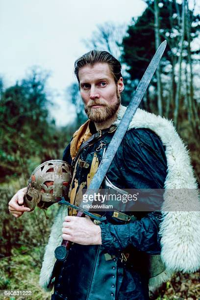 portrait of warrior with beard who holds sword - warrior person stock photos and pictures