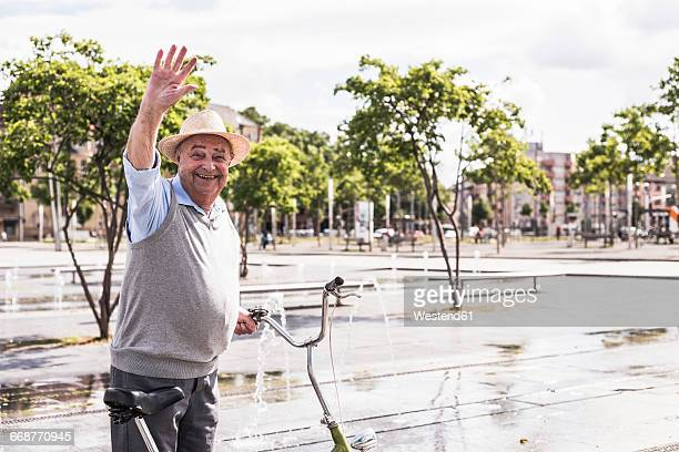 Portrait of waving senior man with folding bicycle
