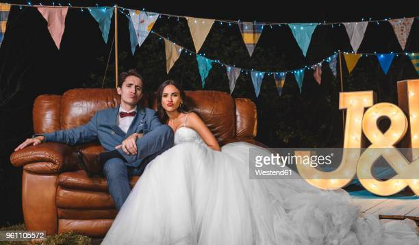 Portrait of wedding couple pouting sitting on sofa on a night field party