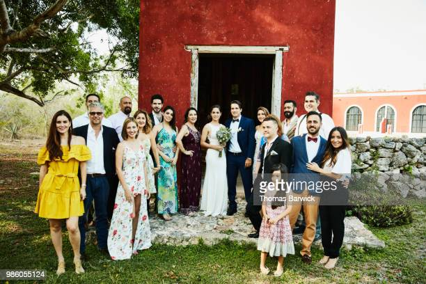 portrait of wedding party standing in front of chapel at tropical resort after wedding ceremony - wedding after party stock pictures, royalty-free photos & images