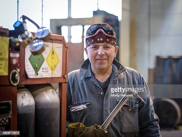 Portrait of welder in overalls and safety goggles in factory