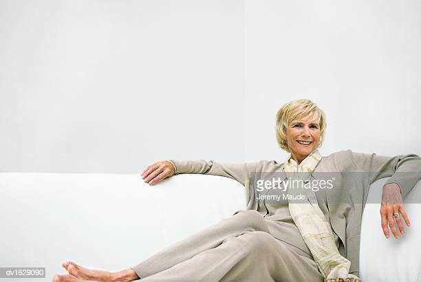 Portrait of Well Dressed Mature Woman Relaxing on a White Sofa