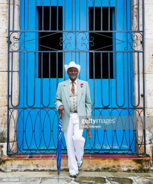 Portrait of well-dressed Black man in front of gated door